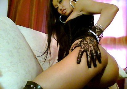 Sweet-looking Asian chick Tyra in black lingerie stands doggy style showing her nice round ass.